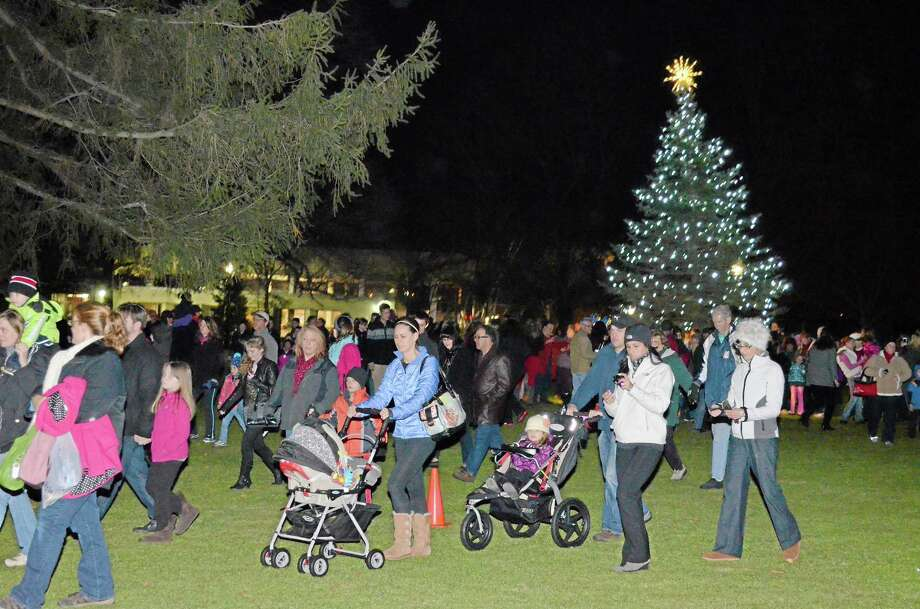 Attendees of the Light Up Main event on Friday make their way from the tree in Coe Memorial Park toward the next event as the procession made stops all the way up Main Street in Torrington. Photo: File Photo — Register Citizen