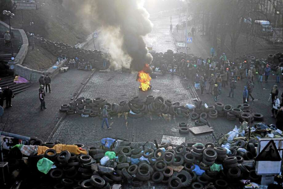 A fire burns at the barricades on the outskirts of Independence Square in Kiev, Ukraine, Friday, Feb. 21, 2014. Ukraineís presidency said Friday that it has negotiated an international deal intended to end battles between police and protesters that have killed scores and injured hundreds. (AP Photo/ Marko Drobnjakovic) Photo: AP / AP