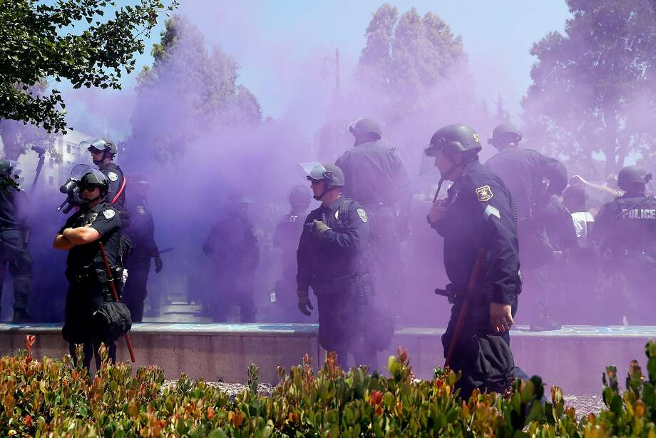 Berkeley Police stand guard as a smoke bomb is set off at Civic Center Park in Berkeley, Calif. on Sunday, August 27, 2017. Photo: Scott Strazzante, The Chronicle