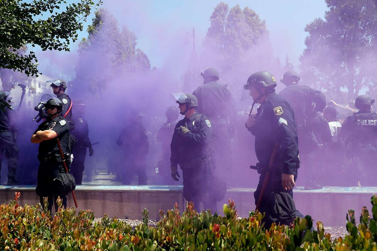 Berkeley Police stand guard as a smoke bomb is set off at Civic Center Park in Berkeley, Calif. on Sunday, August 27, 2017.