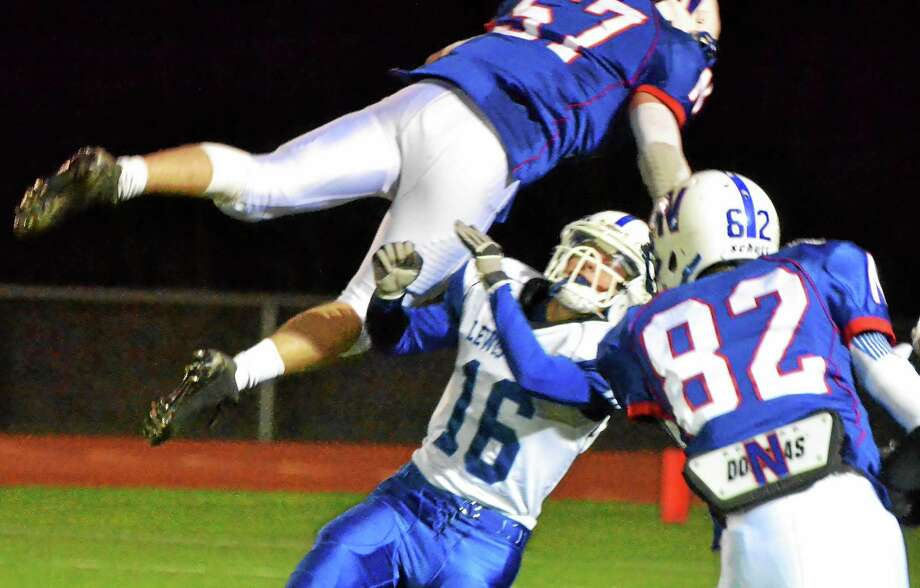 Nonnewaug's R.J. Burke jumps over Lewis Mills punter Tyler Trask after Burke blocked Trask's punt in the Chiefs' 38-7 win over the Spartans. Photo: Pete Paguaga — Register