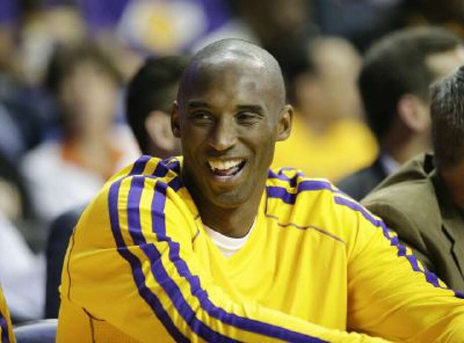 Los Angeles Lakers' Kobe Bryant smiles in the first half of an NBA preseason basketball game against the Denver Nuggets on Tuesday, Oct. 8, 2013, in Ontario, Calif.