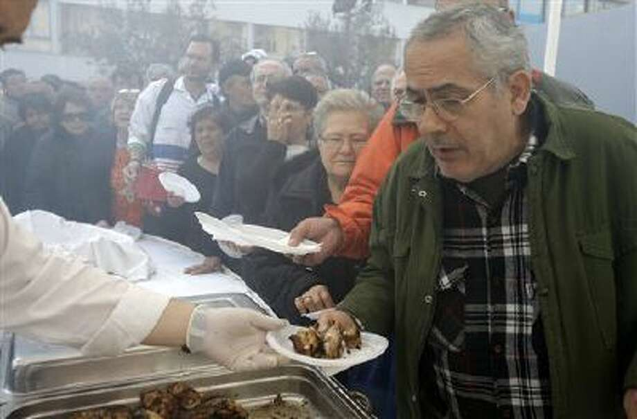 """Hundreds of Athenians queue for free grilled meat at the Athens central meat market, on Thursday, Feb. 20, 2014. The handouts were organized by meat market traders, as part of the annual celebrations for """"Barbecue Thursday"""" _ a raucous pre-Easter celebration for meat lovers. But amid Greece's acute recession and unemployment, the prospect of free meat has come to attract ever-larger crowds. (AP Photo/Thanassis Stavrakis) Photo: AP / AP"""