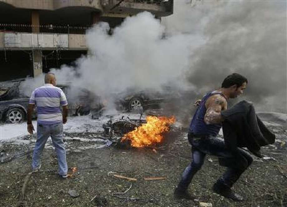 A Lebanese man runs past a burned car at the scene where two explosions have struck near the Iranian Embassy, killing many, in Beirut, Lebanon. Photo: AP / AP