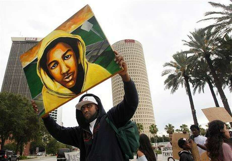 "James Brewton, 39, from Brandon, hoists his portrait of Trayvon Martin along with a group of about 175 as they gather at Curtis Hixon Waterfront Park after marching to the federal courthouse in Tampa on Sunday July 14, 2013, to protest after a jury found George Zimmerman not guilty of murder in the killing of unarmed black teenager Trayvon Martin last year in Sanford. ""I painted it last week,"" Brewton said. ""I just had a feeling it wasn't going to go right."" Brewton, an artist and toy designer, calls his acrylic on canvas painting ""Innocent Eyes, Hard Streets."" (AP Photo/Tampa Bay Times, Dirk Shadd) Photo: AP / Tampa Bay Times"