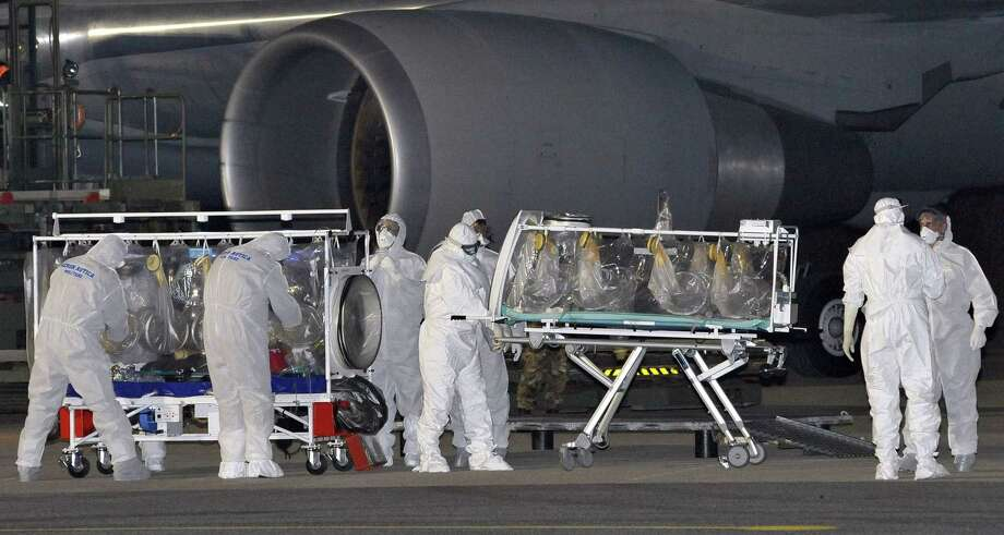 In this photo provided by the Italian Air Force, a KC 767 plane is parked on the tarmac as personnel in biohazard suits work by a stretcher encased in a plastic seal, left, carrying a doctor who has tested positive for the Ebola virus, at the Pratica di Mare military airport near Rome, Tuesday, Nov. 25, 2014. The Italian health ministry says an Italian doctor working in Sierra Leone has tested positive for the Ebola virus and has been transferred to Rome for treatment. The ministry said in a statement that the doctor, who works for the non-governmental organization Emergency, will be taken Monday for treatment at the Lazzaro Spallanzani National Institute for Infectious Diseases in Rome. It is Italy's first confirmed case of Ebola. (AP Photo/Italian Air Force) Photo: AP / Italian Air Force