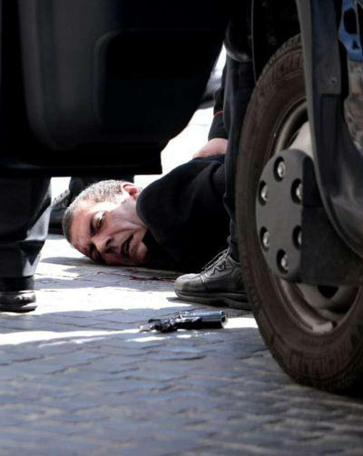 A man believed to be the assailant lies on the ground detained by police after a shootout outside the Chigi Premier's office, in Rome, Sunday, April 28, 2013. Reports say two paramilitary police officers were shot and wounded outside the Italian premier's office as the new leader Enrico Letta was sworn in about a kilometer (half-mile) away. It was unclear if there was any connection between the events. (AP Photo/Mauro Scrobogna, Lapresse) ITALY OUT Photo: ASSOCIATED PRESS / AP2013