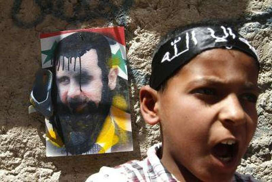 A boy shout slogans as a shoe hangs on the picture of Syria's President Bashar al-Assad behind him ,during a protest against al-Assad after Friday prayers in Raqqa province, east Syria April 26, 2013. (REUTERS/Nour Kelze) Photo: REUTERS / X80002