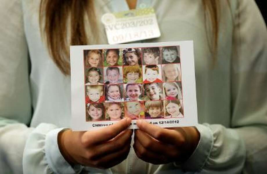 WASHINGTON, DC - SEPTEMBER 18: Kyra Murray holds a photo with victims of the shooting at Sandy Hook Elementary School during a press conference at the U.S. Capitol calling for gun reform legislation and marking the 9 month anniversary of the shooting September 18, 2013 in Washington, DC. With the shooting at the Washington Navy Yard earlier this week, gun reform activists are renewing their call for national reformation of existing gun laws. (Photo by Win McNamee/Getty Images) Photo: Getty Images / 2013 Getty Images