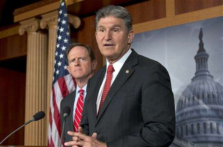 """FILE - In this April 10, 2013 file photo, Sen. Joe Manchin, <a href=""""http://D-W.Va"""">D-W.Va</a>., right, accompanied by Sen. Patrick Toomey, R-Pa., announce that they have reached a bipartisan deal on expanding background checks to more gun buyers,, on Capitol Hill in Washington. The number of Republican senators who might back expanded background checks is now dwindling, threatening a bipartisan effort to subject more gun buyers to the checks. A vote on the compromise, the heart of Congress' gun control effort, is expected this week.  (AP Photo/J. Scott Applewhite, File) Photo: AP / AP"""