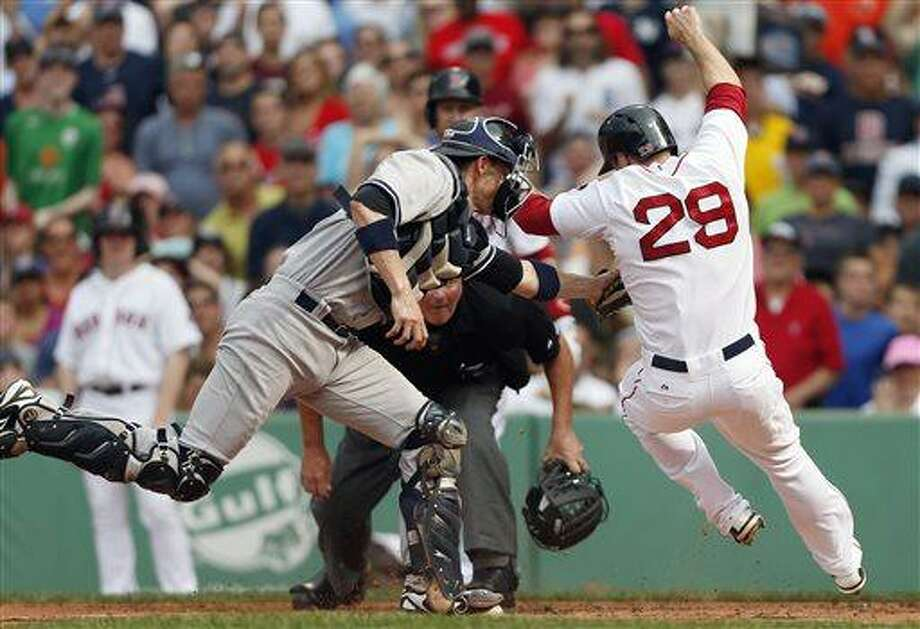 New York Yankees' Chris Stewart, left, tags out Boston Red Sox's Daniel Nava in the first inning of a baseball game in Boston, Saturday, July 20, 2013. (AP Photo/Michael Dwyer) Photo: AP / AP