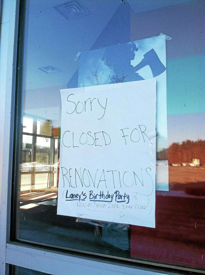 Signs on the doors and windows of the abandoned Mallory Brook Cinema Nine in Barkhamsted. Photo: Jenny Golfin—Register Citizen