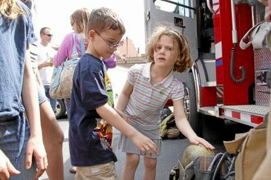Siblings Sam and Savannah Ormezzano touch some fire equipment during a fire safety demonstration by the Torrington Fire Department at KidsPlay in Torrington on Sunday. About 30 people showed up the event held in the afternoon.  ESTEBAN L. HERNANDEZ/REGISTER CITIZEN