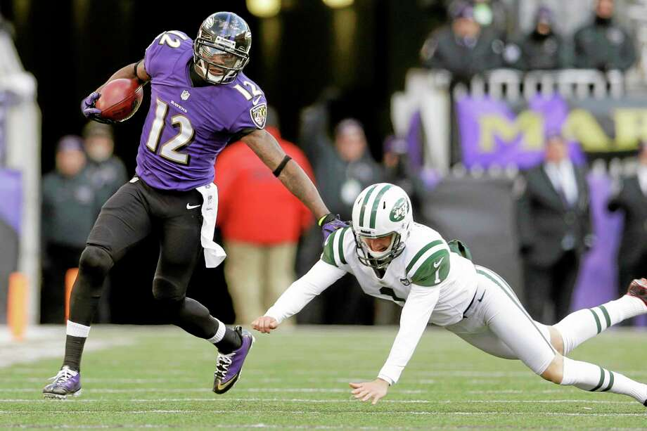 Ravens wide receiver Jacoby Jones, left, outruns Jets punter Ryan Quigley on a return during the second half Sunday. Photo: Patrick Semansky — The Associated Press  / AP