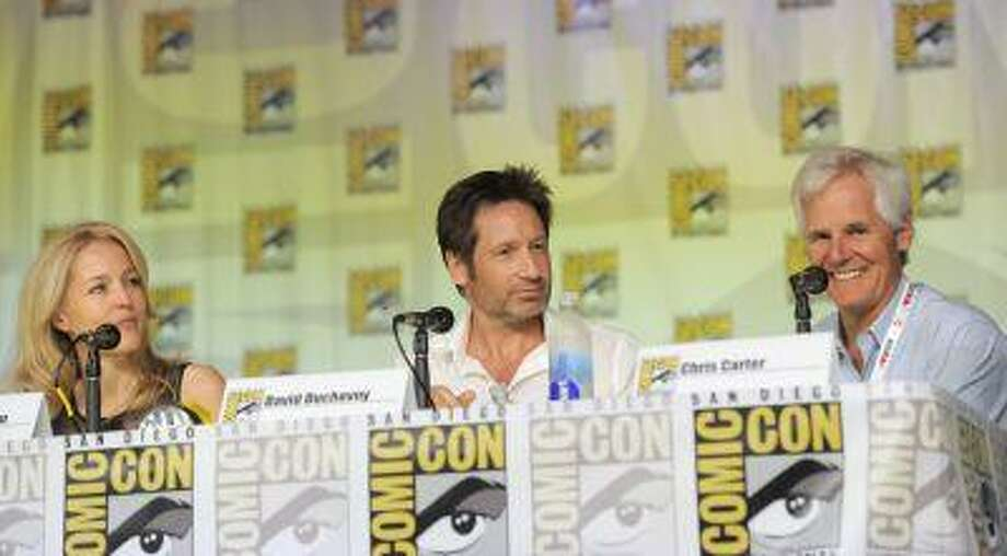 """Gillian Anderson, left, David Duchovny, center, and Chris Carter attend the """"The X Files"""" 20th Anniversary panel on Day 2 of Comic-Con International on Thursday, July 18, 2013 in San Diego, Calif. (Chris Pizzello/Invision/AP) Photo: Chris Pizzello/Invision/AP / AP2013"""
