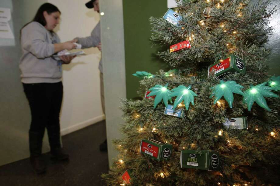 In this photograph taken on Nov. 20, 2014, a Christmas tree decorated with lighted marijuana leaves sits in the foreground as bud tenders Maggie Slattery, back left, and John Satterfield check over customer's order in a recreational marijuana shop in northwest Denver. Photo: AP Photo/David Zalubowski  / AP