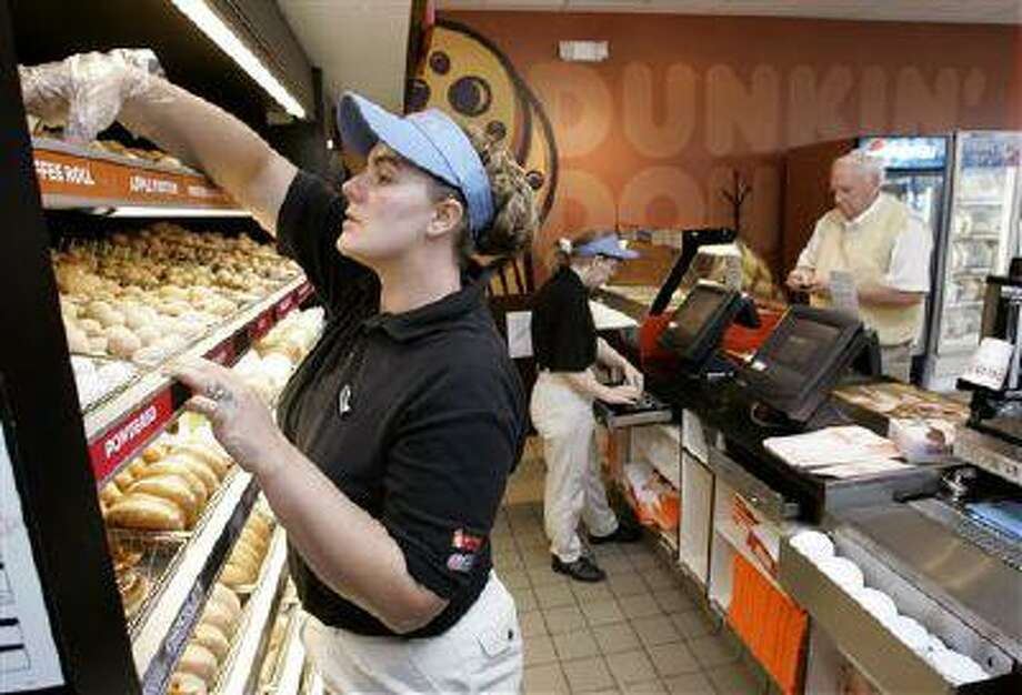In this Oct, 19, 2006 file photo Frankie Morris, left, fills a costumer's order at the Dunkin' Donuts store, in Franklin, Tenn. Dunkin' Donuts offers seniors who purchase a large or extra-large beverage a free doughnut, but you have to show your AARP card. (AP) Photo: AP / AP