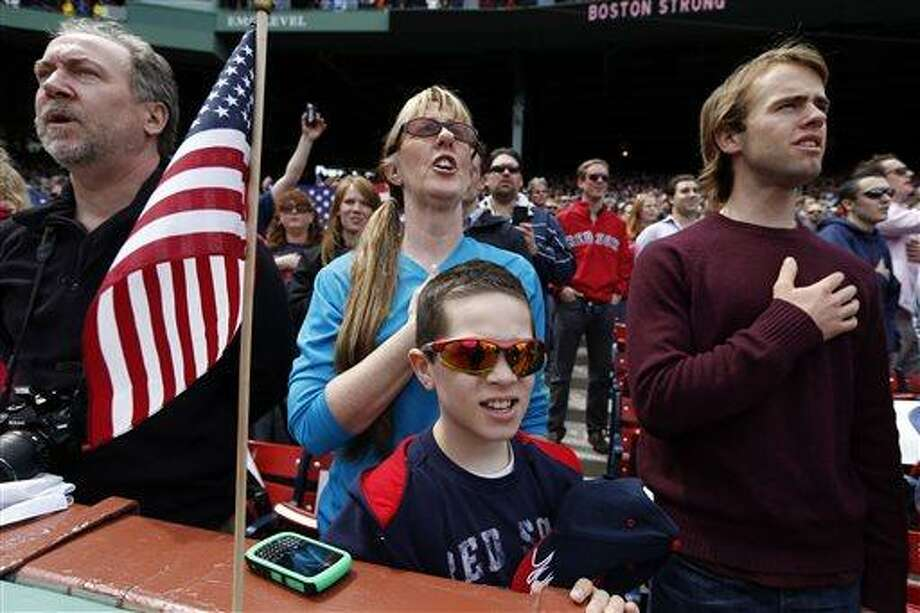 Fans, accompanied by the stadium organist, sing the national anthem before a baseball game between the Boston Red Sox and the Kansas City Royals in Boston, Saturday, April 20, 2013. (AP Photo/Michael Dwyer) Photo: ASSOCIATED PRESS / AP2013
