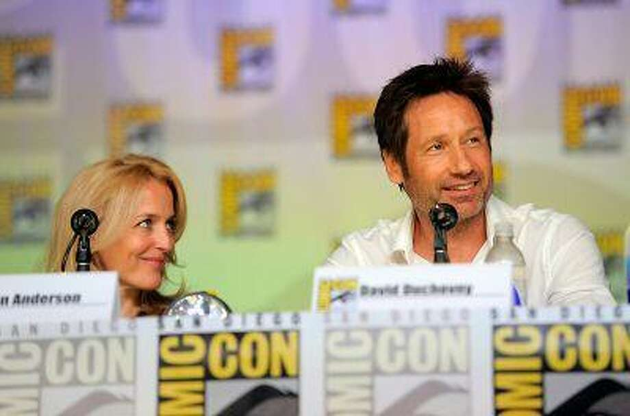 """Gillian Anderson, left, and David Duchovny attend the """"The X Files"""" 20th Anniversary panel on Day 2 of Comic-Con International on Thursday, July 18, 2013 in San Diego, Calif. (Photo by Chris Pizzello/Invision/AP) Photo: Chris Pizzello/Invision/AP / Invision net"""
