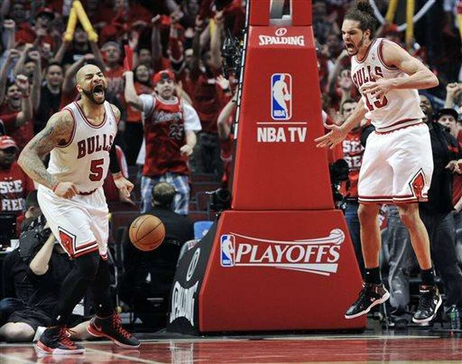 Chicago Bulls' Carlos Boozer (5) and Joakim Noah (13) celebrate a basket against the Brooklyn Nets during the second overtime in Game 4 of their first-round NBA basketball playoff series Saturday, April 27, 2013, in Chicago. The Bulls won 142-134 in three overtimes. (AP Photo/Jim Prisching) Photo: AP / FR59933 AP