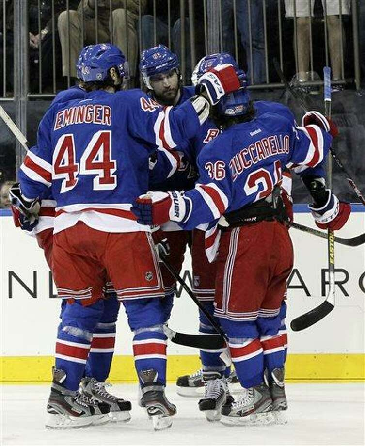 New York Rangers' Rick Nash, center, celebrates with his teammates after scoring a goal during the second period of an NHL hockey game against the New Jersey Devils, Saturday, April 27, 2013 at Madison Square Garden in New York. The Rangers won 4-0. (AP Photo/Mary Altaffer) Photo: AP / AP