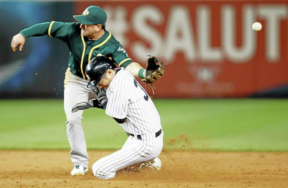 The throw hops past Oakland Athletics second baseman Nick Punto as New York Yankees Ichiro Suzuki (31) is safe stealing second on a sixth inning stolen base in a baseball game at Yankee Stadium in New York, Wednesday, June 4, 2014.  Ichiro advanced to third on the error. (AP Photo/Kathy Willens) Photo: The Associated Press  / AP