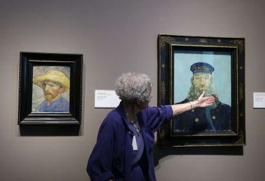 In a June 13, 2013 photo, Detroit Institute of Arts docent Lea Schelke points out details in the Portrait of Postman Roulin by Van Gogh displayed at the museum in Detroit. In a quest to balance the budget in cash-strapped Detroit, the city's emergency manager is proposing a controversial idea: sell the city's art. (AP Photo/Carlos Osorio) Photo: ASSOCIATED PRESS / AP2013