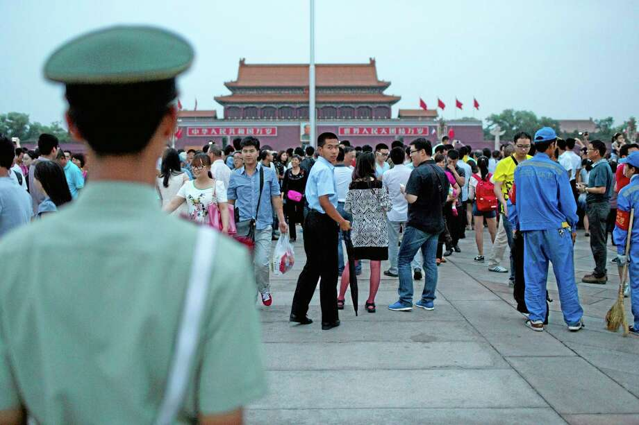 A paramilitary policeman in plain clothes with an umbrella, center, looks back as his uniformed comrade, foreground left, holds his position during a flag-lowering ceremony on Tiananmen Square in Beijing, China, Wednesday, June 4, 2014. Heavy security blanketed central Beijing on the 25th anniversary of the bloody suppression of the Tiananmen Square pro-democracy protests on Wednesday, pre-empting any attempts to publicly commemorate one of the darkest chapters in recent Chinese history. (AP Photo/Alexander F. Yuan) Photo: AP / AP