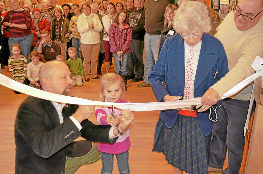 Wayne Foster, building committee chair, helped 4-year-old Johanna Stolfi, the youngest congregation member present, and Sylvia Wadhamas, the oldest member present, cut the ribbon on the Lauper Christian Learning Center. Photo: Kate Hartman—Register Citizen