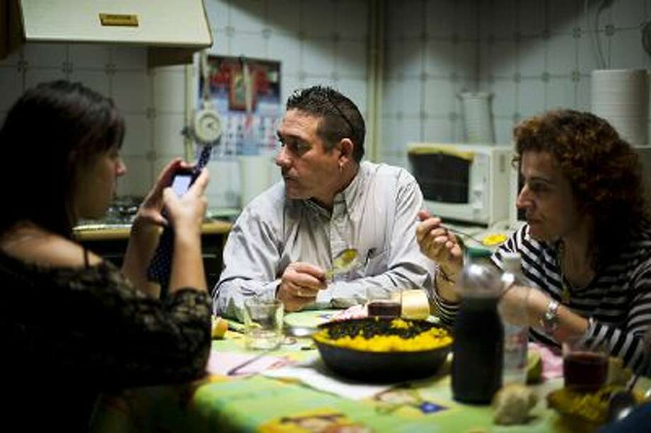 VILLACANAS, SPAIN - NOVEMBER 23:  Forty-eight year old former door factory worker Angel Perez Fernandez (C) eats Paella together with his forty-year old wife, Maria Regine Bueno Villar (R), who worked as a cleaning lady at door factories, and their unemployed twenty-year daughter Maria Regina, at the home of his mother in law on November 23, 2012 in Villacanas, Spain. During the boom years, where in its peak Spain built some 800,000 houses a year accompanied by the manufacturing of millions of wooden doors where needed, the people of Villacanas were part of Spain's middle class enjoying high wages and permanent jobs. During the construction boom years the majority of the doors used within these new developments were made in this small industrial town. Approximately seven million doors a year were once assembled here and the factory employed a workforce of almost 5700 people, but the town is now left almost desolate with the Villacanas industrial park now empty and redundant. With Spain in the grip of recession and the housing bubble burst, Villacanas is typical of many former buoyant industrial Spanish towns now struggling with huge unemployment problems.  (Photo by Jasper Juinen/Getty Images) Photo: Getty Images / 2012 Getty Images