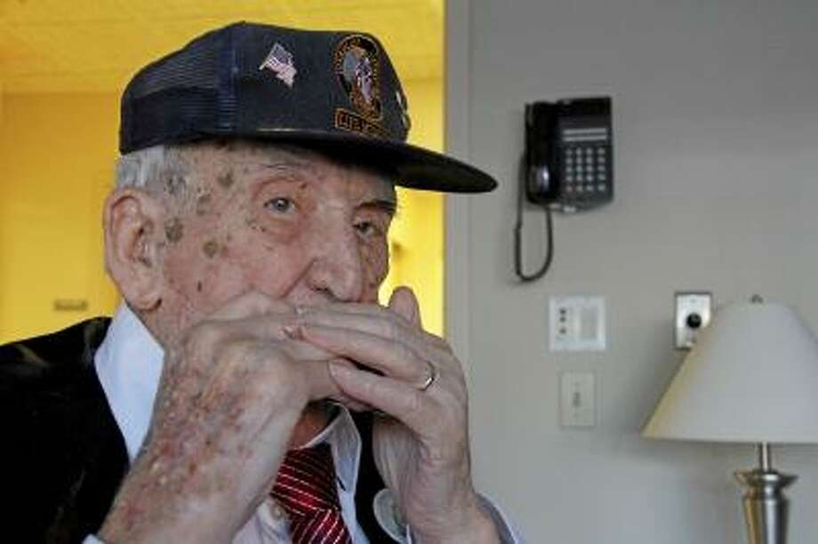 """ESTEBAN L. HERNANDEZ/REGISTER CITIZEN William """"Bill"""" Linden plays his harmonica on Saturday, April 27, 2013, as he celebrated his 100th birthday at Litchfield Woods Health Care Center in Torrington. More than 30 of his family members and close friends were in attendance."""