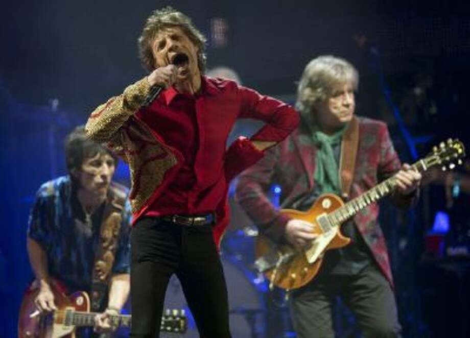 n this June 29, 2013 file photo Mick Jagger, center, Ronnie Wood, left, and Mick Taylor, of British rock band The Rolling Stones, perform on the Pyramid main stage at Glastonbury, England.