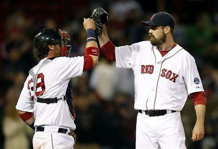 Boston Red Sox's Jarrod Saltalamacchia, left, and Andrew Miller celebrate after defeating the Houston Astros 8-4 in a baseball game in Boston, Saturday, April 27, 2013. (AP Photo/Michael Dwyer) Photo: AP / AP