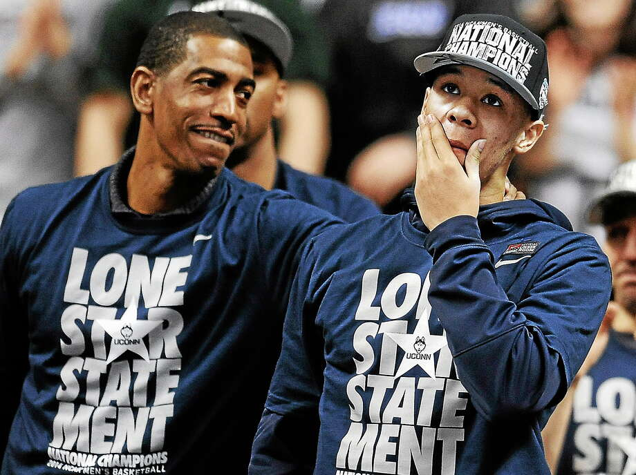 Connecticut's Shabazz Napier, right, reacts as his name is revealed on the Huskies Wall of Honor as coach Kevin Ollie, left, looks over at Napier during a pep rally celebrating Connecticut's fourth NCAA men's basketball championship on April 8, 2014, in Storrs, Conn. Photo: AP Photo/Jessica Hill  / FR125654 AP