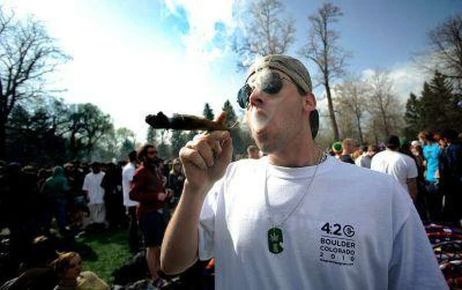 Garrett Kramer smokes a large blunt during the 4/20 event on Norlin Quad at the University of Colorado in Boulder, Colo., April 20, 2010. Photo: DP / Daily Camera
