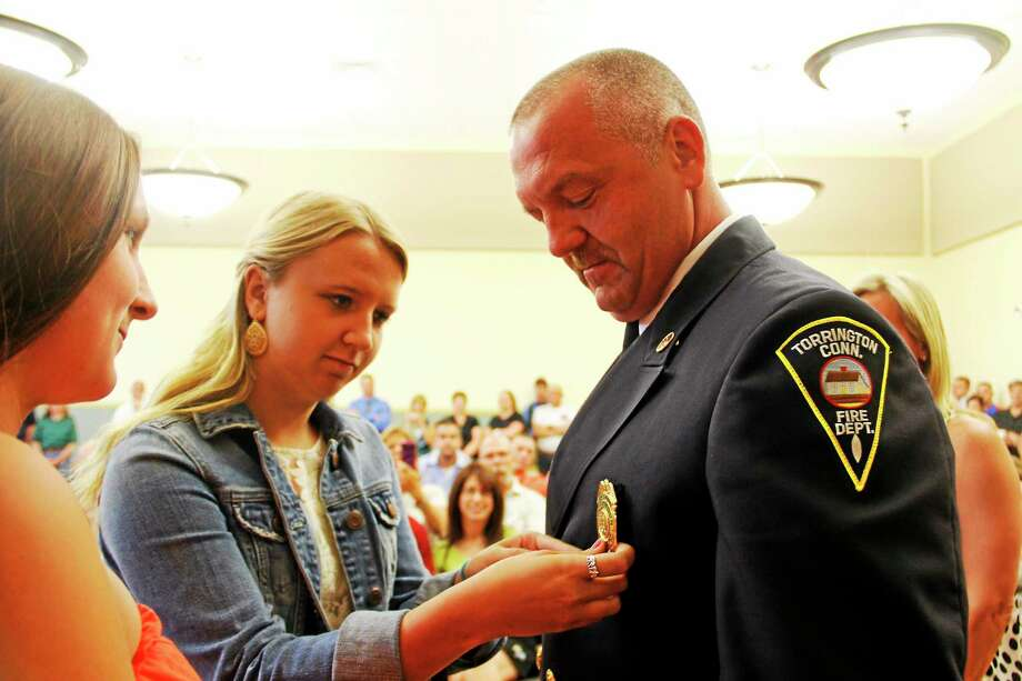Ashley Doyle pins a new badge on her father, Capt. Patrick Doyle of the Torrington Fire Department, as her sister, Shannon, looks on during a pinning ceremony on Wednesday in Torrington. The ceremony involved three pinning during the Board of Public Safety's meeting, giving the firefighters a new badge after their promotions last month. Photo: Esteban L. Hernandez — Register Citizen