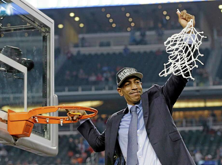 UConn men's basketball coach Kevin Ollie cuts down the net after the Huskies' 60-54 victory over Kentucky in national championship game on April 7 in Arlington, Texas. Photo: David J. Phillip — The Associated Press  / AP