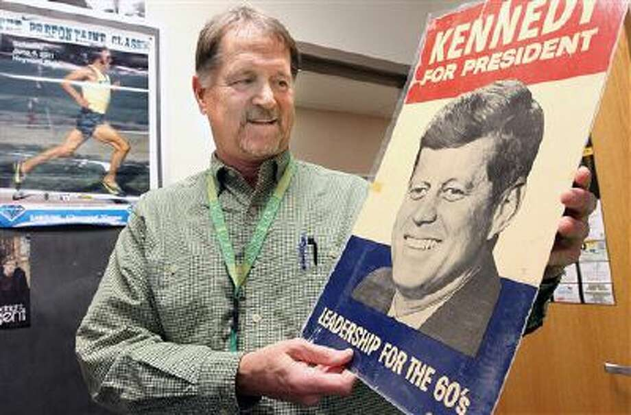 Jim Qualheim holds a copy of President John F. Kennedy's 1960 campaign-for-president sign he received when he was 12 years old while going door to door spreading leaflets with his family. Photo: AP / The Tri-City Herald