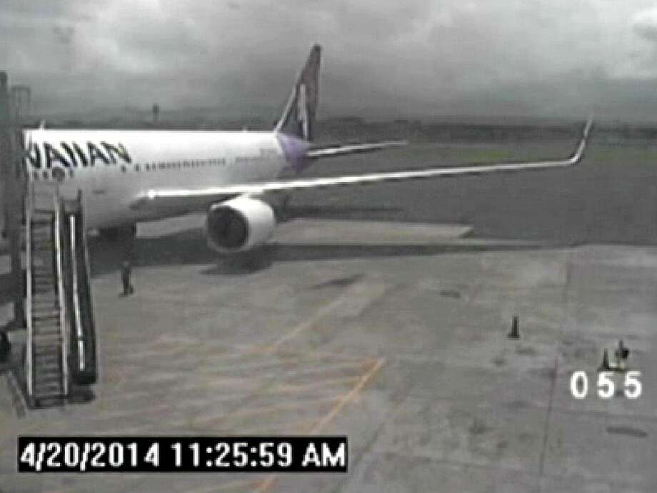 FILE - In this April 20, 2014, file image taken from a surveillance video provided by the Hawaii Department of Transportation, shows a California teen, left, after hopping from a jet's wheel well in Maui, Hawaii. When it was time for that same jet to leave, the pilot, who was a different pilot than the one who had landed the jet there, said security and mechanics were holding him up, according to a ten minute Federal Aviation Administration audio recording, provided exclusively to The Associated Press in response to a Freedom of Information Act request. (AP Photo/Hawaii Department of Transportation, File) Photo: AP / Hawaii Department of Transportation
