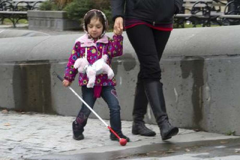 Zoe Newton, 5, with her mother Kellie, is legally blind and has been diagnosed with a rare bone disease. Her family wants her to continue getting care from Seattle Children's Hospital, but it is out of network for many of the insurance plans offered through Washington state's health exchange.