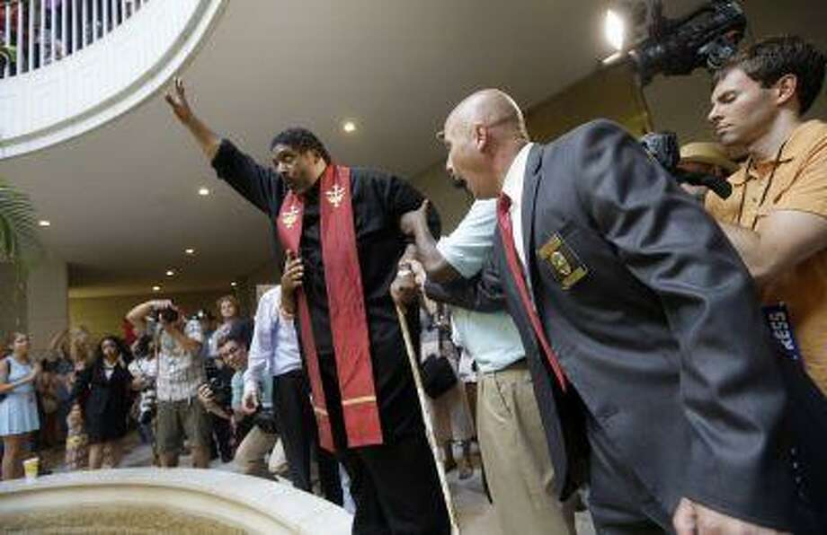 """General Assembly Police Lt. Martin Brock, right, directs Rev. William Barber, President of the N.C. chapter of the NAACP to step down during """"Moral Monday"""" demonstrations at the General Assembly in Raleigh, N.C., Monday, July 8, 2013. Nearly 700 people, led by the North Carolina Chapter of the NAACP, have been arrested over the past 10 weeks of the legislative session while protesting against policies being enacted by the North Carolina General Assembly. (AP Photo/Gerry Broome) Photo: AP / AP"""
