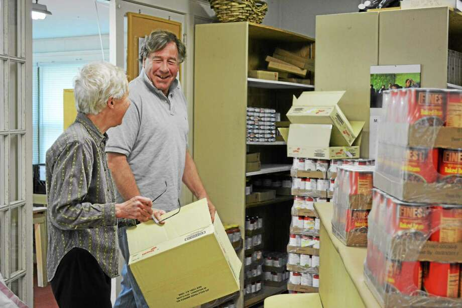Sue Morrill talks with John Borden about the work that needs to be done moving the recent Connecticut Food Bank delivery. Photo: Jenny Golfin - The Register Citizen.