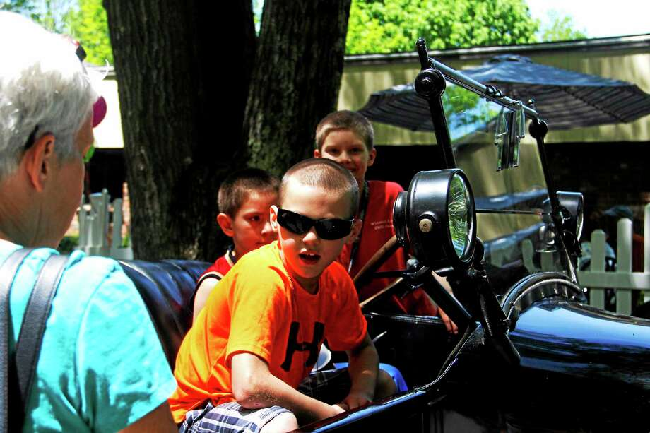 Children ride a vintage automobile during the Touch-A-Truck event at Torrington Health and Rehab on Sunday, June 1, 2014. Photo: Esteban L. Hernandez - The Register Citizen
