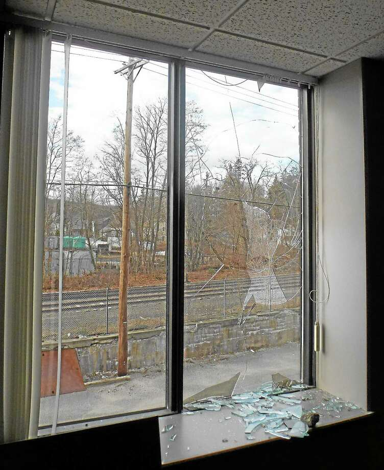 One of the shattered windows at 59 Field St., with a rock visible, on Thursday, Nov. 21, 2013. Vandals have destroyed more than 20 windows, causing more than $30,000 worth of damage. Photo: Esteban L. Hernandez — Register Citizen
