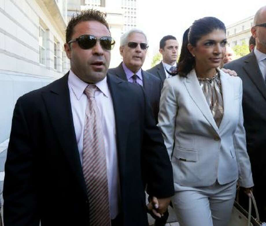 """In this July 30, 2013 photo, """"The Real Housewives of New Jersey"""" stars Giuseppe """"Joe"""" Giudice, left, and his wife, Teresa Giudice, of Montville Township, N.J., walk out of Martin Luther King Jr. Courthouse after an appearance in Newark, N.J."""
