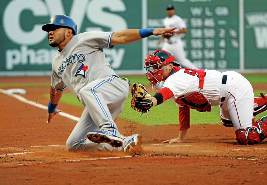 The Blue Jays' Melky Cabrera slides safely into home past Red Sox catcher Christian Vazquez in the first inning Wednesday. Photo: Elise Amendola — The Associated Press  / AP