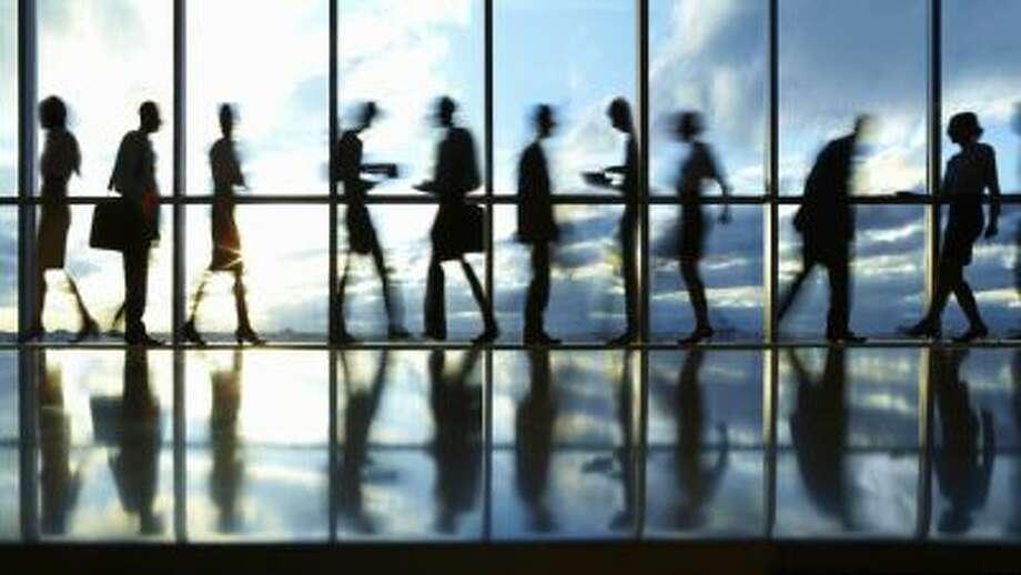 Business people walking in an office corridor.