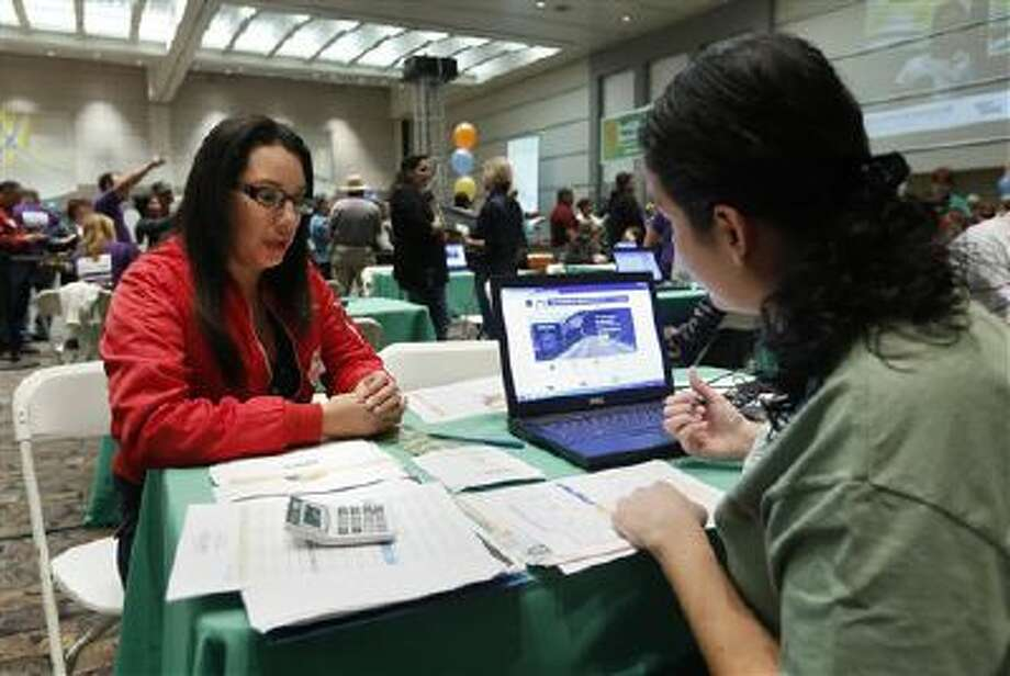 Cinthia Orozco gets help signing up for health insurance from Griselda Zamora, a health care specialist, in Sacramento, Calif. Photo: AP / AP
