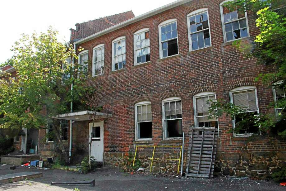 Outside the vacant Lambert Kay property on July 18 in Winsted. The town-owned building is slated to receive $500,000 in grant funding to remediate the site. Photo: Esteban L. Hernandez — The Register Citizen