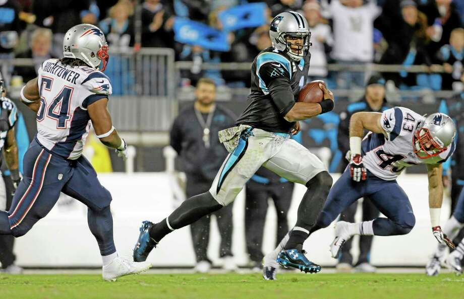 The Panthers' Cam Newton, center, scrambles as the Patriots' Dont'a Hightower, left, and Nate Ebner pursue during the second half of Monday's game in Charlotte, N.C. Photo: Bob Leverone — The Associated Press  / FR170480 AP